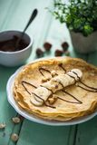 French Crepes or Pancake with Banana and Chocolate. On wood Background stock images