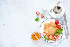 French Crepes or Russian Blini with fresh strawberries, honey, coffee stock images