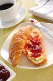 French Croissant. With strawberry jam and butter royalty free stock images