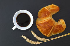 French croissant and coffee on black slate stone plate for morning breakfast or break time Stock Photos