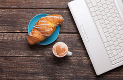 French croissant and cup near laptop Royalty Free Stock Images