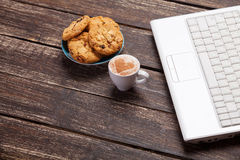 French croissant and cup near laptop Stock Photography