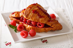 French croissant stuffed with fresh raspberries and jam, close-u. French croissant stuffed with fresh raspberries and jam close-up on the table. Horizontal Royalty Free Stock Photo