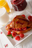 French croissant stuffed with fresh raspberries and jam, orange. Juice and milk close-up on the table. vertical Royalty Free Stock Image