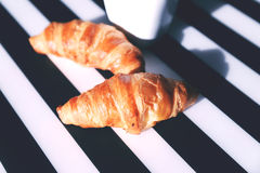 French croissants on the striped table. Baked French croissants on the black and white striped serviette Royalty Free Stock Photos