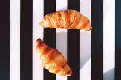 French croissants on the striped table. Baked French croissants on the black and white striped serviette Stock Photo