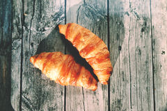 French croissants on the wooden table. Baked French croissants on the wooden table Stock Images