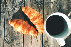 French croissants on the wooden table. Baked French croissants on the wooden table with the cup of black coffee Royalty Free Stock Images