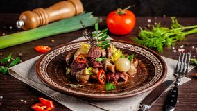 French cuisine concept. blanquette of veal with mushrooms, whole stewed onions, carrots and chilli peppers. Serving dishes. In the restaurant in a ceramic plate royalty free stock photos
