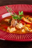 French cuisine concept. Classic French fish soup of seafood, shrimps, mussels, squid, potatoes, tomatoes stock image