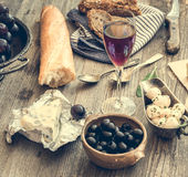 French cuisine. Different types of cheese, wine and other ingredients on a wooden table Royalty Free Stock Photos