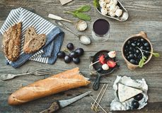 French cuisine. Different types of cheese, wine and other ingredients on a wooden table stock photography