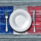 French Cuisine. Food concept as a place setting with knife and fork on an old rustic wood table with a symbol of the flag of France as an icon of traditional Stock Photo