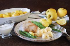 French cuisine: fried pork with Norman apple sauce, green beans and fried potatoes. In ceramic dish. Rustic style royalty free stock images