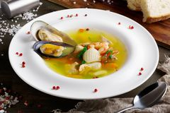 French seafood soup with white fish, shrimps and mussels in plate at wooden background