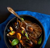 French cuisine: steamed muscles with fresh basil leaves in a black pot together. Steamed muscles with fresh basil leaves in a black pot together with vintage Royalty Free Stock Photography