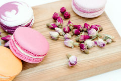 French delicious pink color macarons cookies and small roses on wood desk. Royalty Free Stock Image