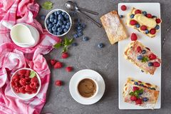 French dessert millefeuille on a plate. French dessert millefeuille of puff pastry and custard cream, raspberries, blueberries on a plate with cup of coffee stock image