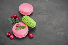 French dessert. Sweet pink and green macaroons or macarons with cranberry and mint. On black concrete background Stock Photo
