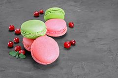 French dessert. Sweet pink and green macaroons or macarons with cranberry and mint. On black concrete background Royalty Free Stock Photo