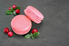 French dessert. Sweet pink macaroons or macarons with cranberry and mint. On black concrete background Royalty Free Stock Image
