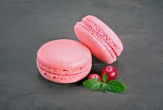 French dessert. Sweet pink macaroons or macarons with cranberry and mint. On black concrete background Royalty Free Stock Photos