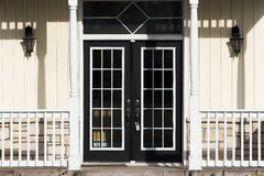 French Doors. Double French doors with porch, pale yellow siding and white trim Stock Photography