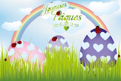 French Easter card with rainbow, eggs in green grass and ladybug Stock Photo