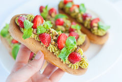 French eclairs with whipped cream and topped with strawberries, Royalty Free Stock Photos