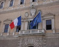 French and European Union flags. Fluttering outside Palazzo Farnese, the French Embassy in Rome. The coat of arms of Farnese Pope Paul III is recognizable stock image