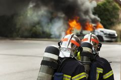 French firefighter binomial attac on car fire. Fireman brigade danger royalty free stock photos