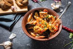 French fish soup Bouillabaisse with seafood, salmon fillet, shrimp, mussels on stone background. Delicious dinner. French fish soup Bouillabaisse with seafood royalty free stock photos