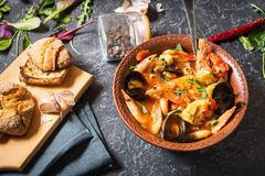 French fish soup Bouillabaisse with seafood, salmon fillet, shrimp, mussels on stone background. Delicious dinner. French fish soup Bouillabaisse with seafood stock photos