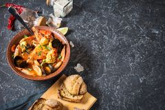 French fish soup Bouillabaisse with seafood, salmon fillet, shrimp, mussels on black stone background. Delicious dinner. Copy space royalty free stock photo
