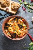 French fish soup Bouillabaisse with seafood, salmon fillet, shrimp, mussels on stone background. Delicious dinner. French fish soup Bouillabaisse with seafood royalty free stock image