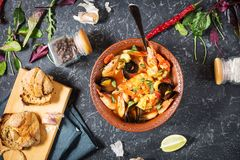 French fish soup Bouillabaisse with seafood, salmon fillet, shrimp, mussels on black stone background. Delicious dinner. Top view stock images