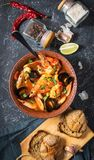 French fish soup Bouillabaisse with seafood, salmon fillet, shrimp, mussels on black stone background. Delicious dinner. Top view stock photos