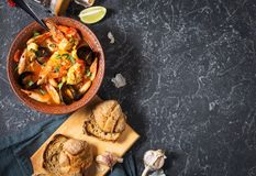 French fish soup Bouillabaisse with seafood, salmon fillet, shrimp, mussels on black stone background. Delicious dinner. Top view and Copy space royalty free stock photography