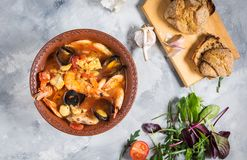 French fish soup Bouillabaisse with seafood, salmon fillet, shrimp, mussels on concrete background. Delicious dinner. Top view stock photography