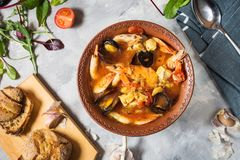 French fish soup Bouillabaisse with seafood, salmon fillet, shrimp, mussels on concrete background. Delicious dinner. Top view royalty free stock images