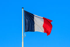 The french flag with blue sky in the background. stock images