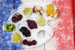 French flag created from splash colours blue white red on a pile of fruit slices on white plastic art palette, wooden background royalty free illustration