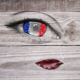 French flag on eye pupil with tear drop, realistic lips on wooden grey background Stock Photo