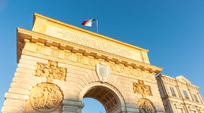 French flag flutters against setting blue sky as low sun casts g. Olden hue on Arch of Triumph at entrance or Porte du Peyrou  triumphal archn Montpellier Stock Photography