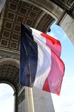 French flag flying under Arc de Triomphe. Large French flag flying under Arc de Triomphe in Paris Royalty Free Stock Photo