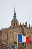 French flag in front of Mont Saint-Michel. The Mont Saint-Michel is a tidal island in Normandy and one of the most visited tourist sites in France royalty free stock photos