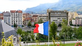 French flag in Grenoble. French flag in the wind in the foreground. Filmed in the city of Grenoble in the Alps, southeaster, France. In the background, there is stock video footage