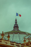 French flag swaying at the top of Grand Palais Royalty Free Stock Photo