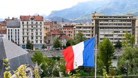 French flag in Grenoble. French flag in the wind. Filmed in the city of Grenoble in the Alps, southeaster, France. In the background, there is moutains stock footage