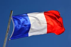 French flag in the wind on a sunny day. With blue sky background stock photography